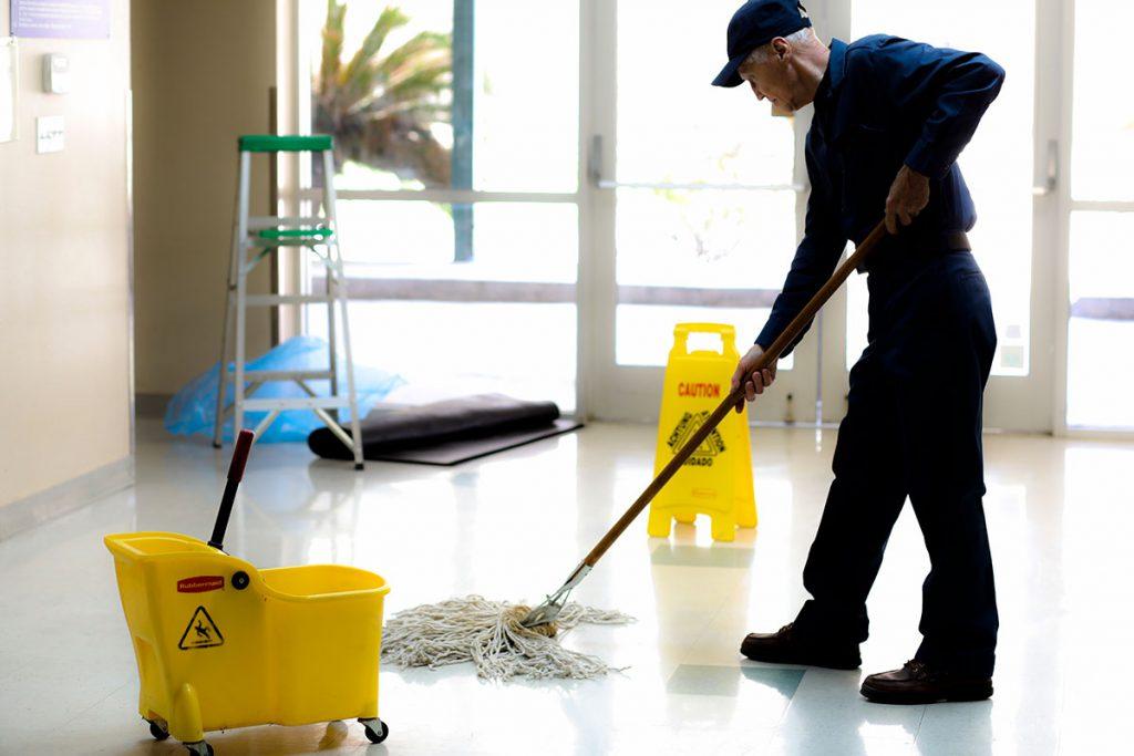 Zelador limpando o chão.