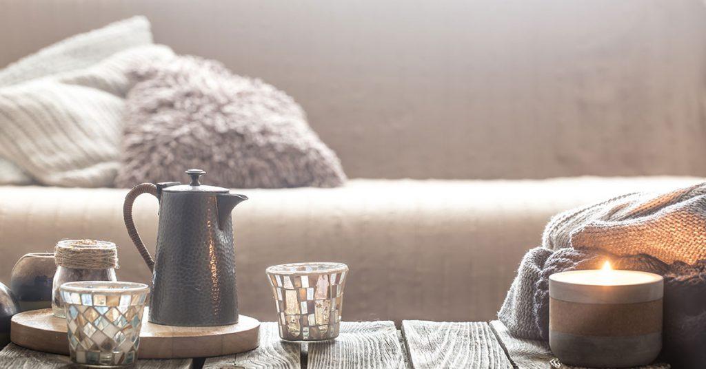 Imagem mostra uma bule com xícaras sob uma mesa de centro e um sofá ao fundo.