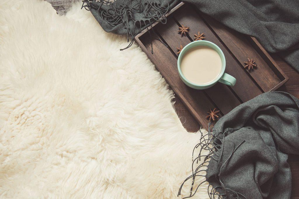Imagem mostra um tapete fofinho de pelo e uma xícara de café