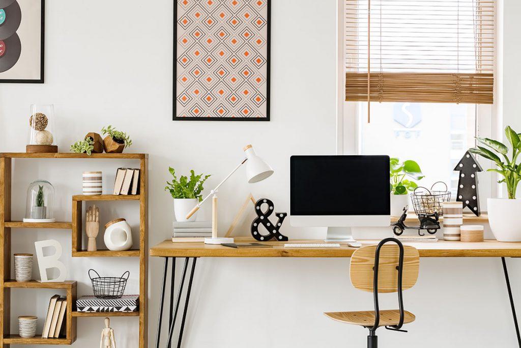 Escritório clean com uma mesa, computador, cadeira e alguns enfeites.
