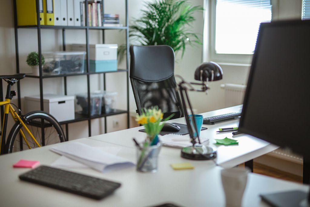 Imagem mostra um escritório com uma cadeira, mesa e uma estante.