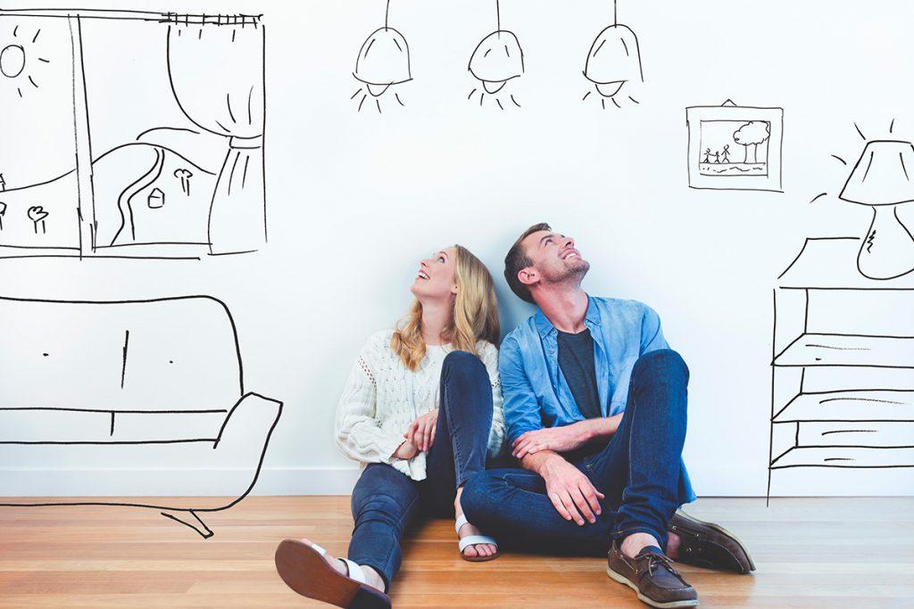 casal sentado no chão sorrindo e vários desenhos na parede em formato de moveis.