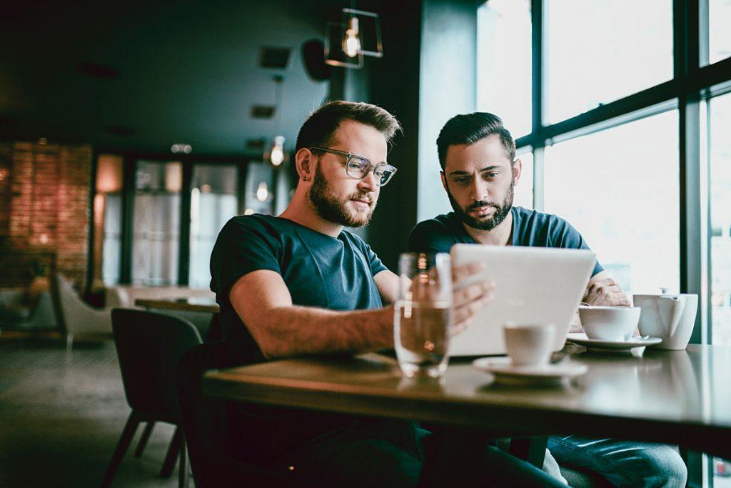 Dois homens sentados em frente ao notebook