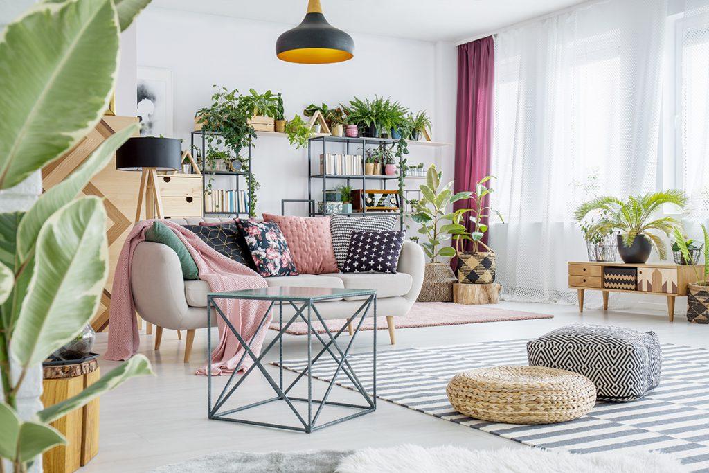 Sala de estar com decoração moderna e varias plantas compondo a decoração