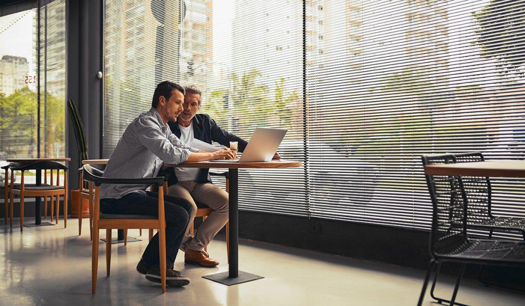 dois homens olhando o notebook em uma mesa de escritório