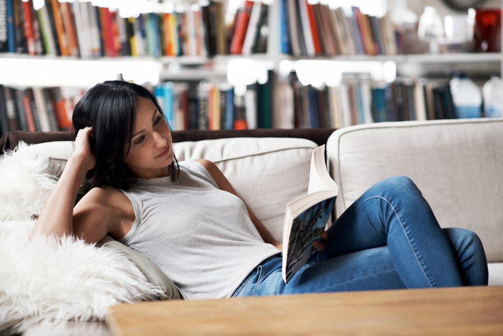 Imagem mostra moça lendo um livro sentada no sofá