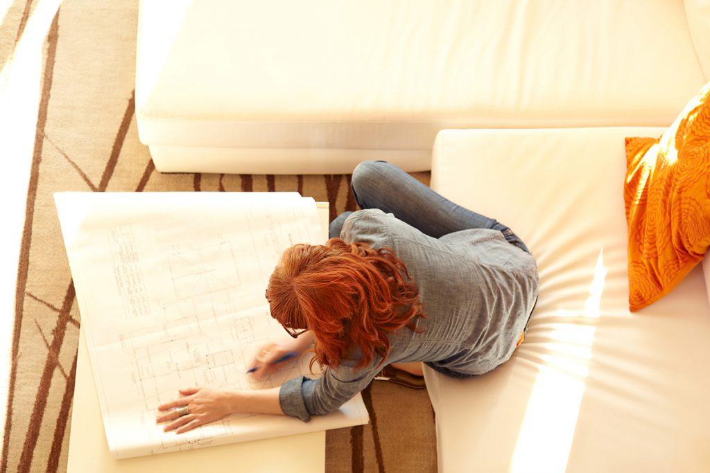 Imagem mostra moça verificando a planta do apartamento.