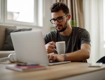imagem de uma pessoa mexendo no notebook e tomando café