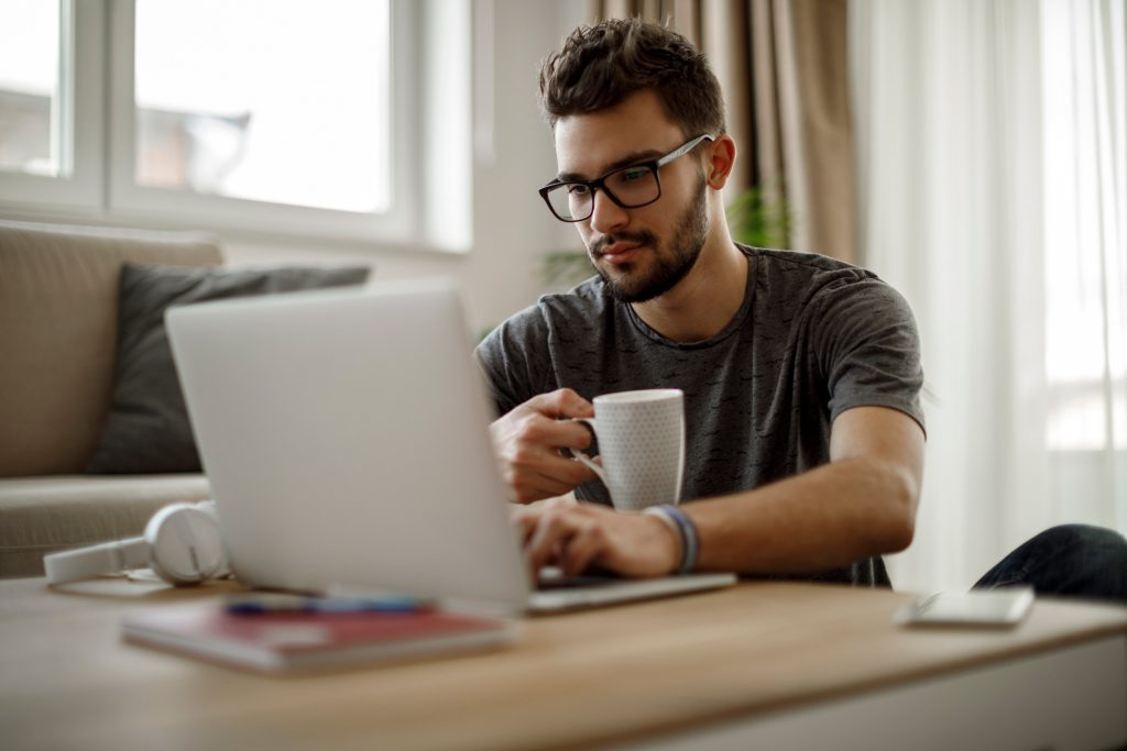 Imagem mostra moço tomando café em frente ao notebook