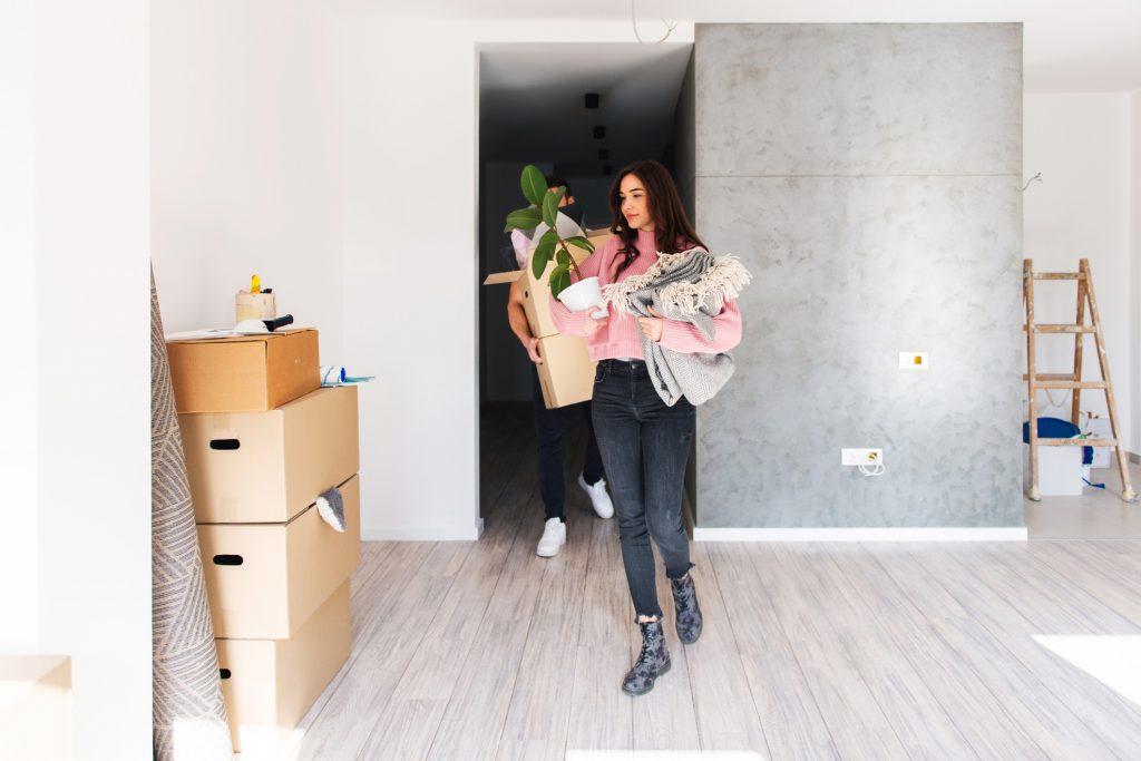 Imagem com menina segurando uns tapetes e um vaso de flor