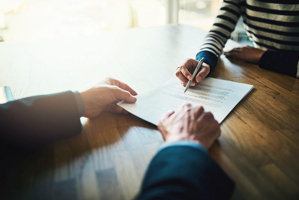 Imagem mostra mulher assinando documentos