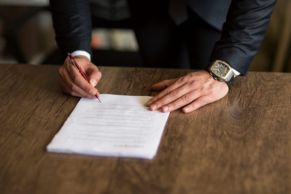 Imagem mostra homem assinando documentos