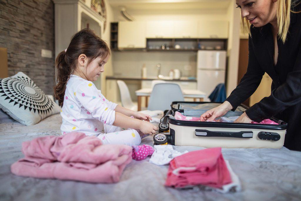 Menina arrumando sua mala com a sua mãe
