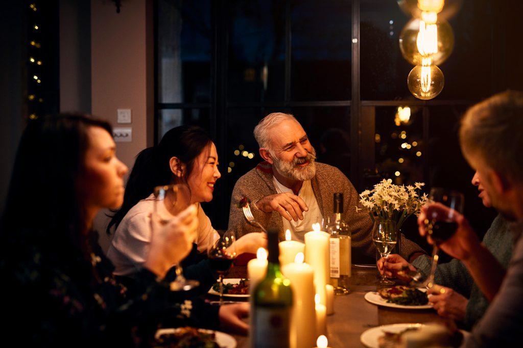 Imagem mostra pessoas sorrindo e jantando