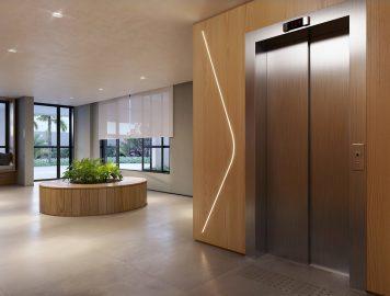 hall social de empreendimento moderno, com elevador à direita da imagem, espaço ao centro com plantas enfeitando o local e sofá ao fundo. À esquerda da imagem, janelas dão para o jardim. A foto retrata um dia ensolarado.